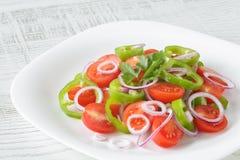Здоровый, свежий и очень вкусный vegetable салат с томатами вишни, кольца красного лука, кольца зеленого перца, петрушка и оливко Стоковое Изображение