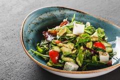 Здоровый свежий салат с авокадоом, зелеными цветами, arugula, шпинатом, томатами вишни и сыром в плите над темной таблицей Здоров стоковое изображение