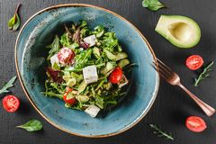 Здоровый свежий салат с авокадоом, зелеными цветами, arugula, шпинатом, томатами вишни и сыром в плите над темной таблицей Здоров стоковые фотографии rf