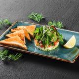 Здоровый свежий салат с авокадоом, семгами, зелеными цветами, arugula, шпинатом и сыром с тостом в плите над темной предпосылкой стоковая фотография rf