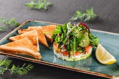 Здоровый свежий салат с авокадоом, семгами, зелеными цветами, arugula, шпинатом и сыром с тостом в плите над темной предпосылкой стоковое изображение rf