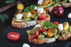 Здоровый тост Advocado с сыром и Pesto моццареллы томатов базилика стоковое изображение