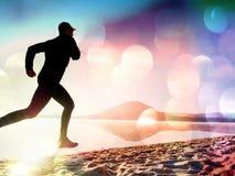 Здоровый уклад жизни Высокорослый бегун молодого человека бежит на взморье восхода солнца Новый барьер Стоковое фото RF