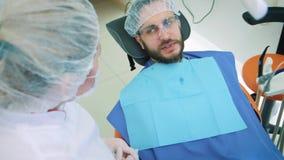 Здоровье и зубоврачебная забота, женщина на работе как дантист и доктор, говоря к мужскому пациенту Обсудите зубоврачебную обрабо видеоматериал