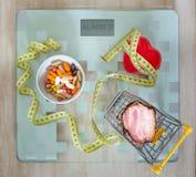 здоровье планшеты, сердце вместе с жирной пищей как концепция полного, плохого питания или стимул к здоровому lifestyl стоковое фото