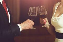 Здравица пар clink стекла с красным вином стоковые фото