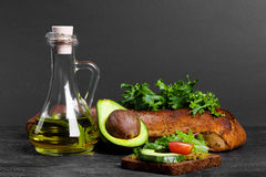 Здравица с гуакамоле, салатом и томатами Авокадо с опарником масла, хлеба и зеленых цветов на предпосылке таблицы скопируйте косм Стоковая Фотография