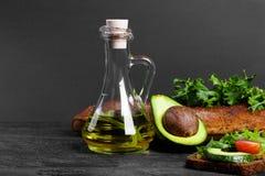 Здравица с гуакамоле, салатом и томатами Авокадо с опарником масла, хлеба и зеленых цветов на предпосылке таблицы скопируйте косм Стоковое Изображение