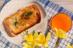 Здравица с маслом и сыром на белой плите, стекле оранжевого jui Стоковая Фотография