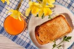 Здравица с маслом и сыром на белой плите, стекле оранжевого jui Стоковое Изображение