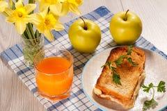 Здравица с маслом и сыром на белой плите, 2 яблоках, стекле o Стоковые Изображения RF