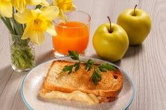 Здравица с маслом и сыром на белой плите, 2 яблоках, стекле o Стоковое фото RF