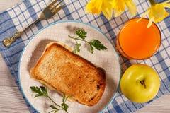 Здравица с маслом и сыром на белой плите, яблоке, стекле ora Стоковые Изображения RF