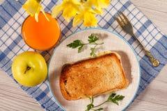 Здравица с маслом и сыром на белой плите, яблоке, стекле ora Стоковое Изображение RF