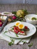 Здравица с яичком, красным перцем, сыром и rucola на белой плите стоковая фотография