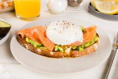 Здравица хлеба Wholemeal, поломанный авокадо, семги и краденное яичко Стоковое Фото