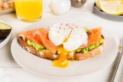 Здравица хлеба Wholemeal, поломанный авокадо, семги и краденное яичко Стоковое Изображение RF