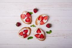 Здравицы или bruschetta с клубниками на плавленом сыре на белой деревянной предпосылке Стоковое Изображение
