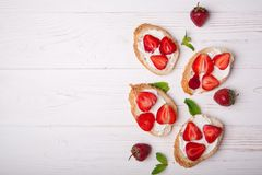 Здравицы или bruschetta с клубниками на плавленом сыре на белой деревянной предпосылке Стоковое фото RF