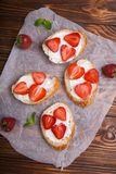 Здравицы или bruschetta с клубниками на плавленом сыре на деревянной предпосылке Стоковая Фотография RF