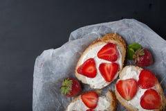 Здравицы или bruschetta с клубниками на плавленом сыре на черной предпосылке Стоковые Фото