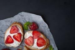 Здравицы или bruschetta с клубниками на плавленом сыре на черной предпосылке Стоковая Фотография RF