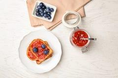 Здравицы с вареньем и ягодами на деревянной предпосылке Стоковая Фотография RF