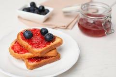 Здравицы с вареньем и ягодами на плите Стоковые Изображения