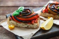 Здравицы с испеченными aubergines и перцами на деревянной доске, деревенском стиле Стоковое Изображение
