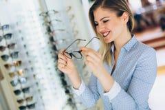 Здравоохранение, зрение и концепция зрения - счастливая женщина выбирая стекла на магазине оптики Стоковая Фотография