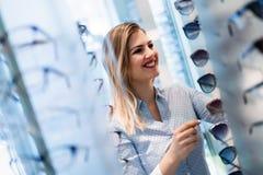 Здравоохранение, зрение и концепция зрения - счастливая женщина выбирая стекла на магазине оптики Стоковые Фотографии RF
