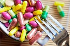 Здравоохранение и здоровье - пилюльки диеты и вес освобождать - различные таблетки в баке с вилками стоковая фотография