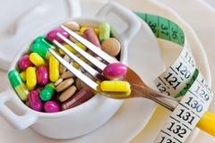 Здравоохранение и здоровье - пилюльки диеты и вес освобождать - различные таблетки в баке с вилками стоковые фотографии rf