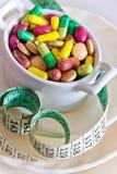 Здравоохранение и здоровье - пилюльки диеты и вес освобождать - различные таблетки в баке с измеряя метром стоковые изображения rf