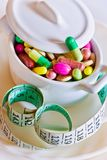 Здравоохранение и здоровье - пилюльки диеты и вес освобождать - различные таблетки в баке с измеряя метром стоковые фото