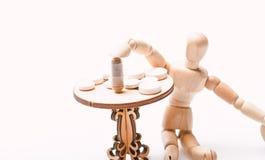 Здравоохранение и медицинское лечение Таблетки на крошечном деревянном столе Режим лекарства Человеческий деревянный манекен окол стоковое изображение