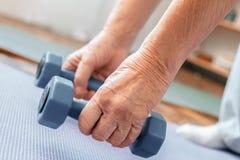 Здравоохранение тренировки старшего человека дома держа конец-вверх гантелей вниз Стоковые Изображения
