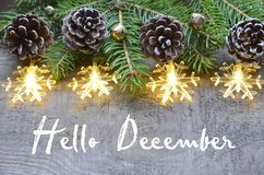 Здравствуйте! декабрь Украшение рождества с елью, конусами сосны и светами гирлянды на старой деревянной предпосылке стоковая фотография rf