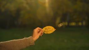 Здравствуйте осень написанная на желтых лист, руке держа сочинительства, яркий золотой сезон стоковое изображение rf