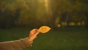 Здравствуйте падение написанное на желтых лист, руке держа сочинительства, золотой сезон осени стоковое изображение