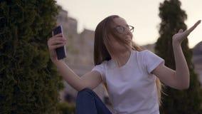 Здравствуйте там! Маленькая девочка развевает к экрану к ее парню в камере пока имеющ видео- парк звонка весной сток-видео