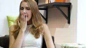 Зевая жест милой красивой девушкой, сидеть утомлянный на работе сток-видео
