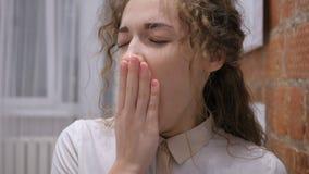 Зевая утомленное молодое женское усаживание в офисе видеоматериал