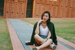 Зеленая женщина рубашки сидя на лужайке стоковые фото