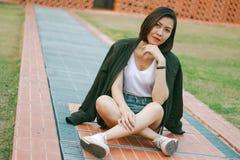 Зеленая женщина рубашки сидя на лужайке стоковое фото rf