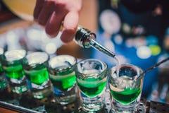 Зеленая жидкость в стопках стоя на счетчике бармен подготавливая съемки стоковые фото