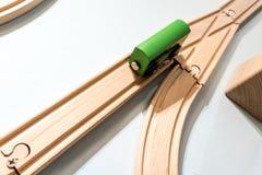Зеленая игрушка автомобиля на деревянном следе изолированном на белизне Стоковые Фото