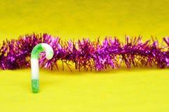 Зеленая и белая тросточка конфеты с фиолетовым tinsell Стоковые Фото