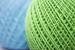 Зеленая и голубая пряжа для вязать на белой предпосылке Стоковые Изображения