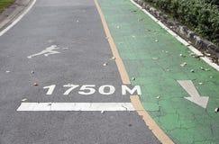 Зеленая майна велосипеда и белая стрелка крася параллельными с jogging майной и белым jogging укомплектовывают личным составом ка стоковые фотографии rf